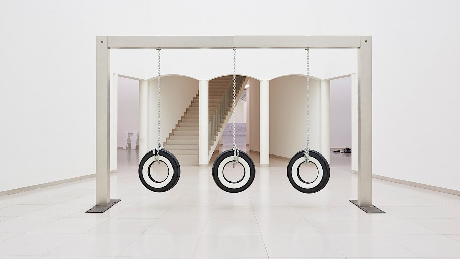 Three tires hang on chains, which themselves hang from an metallic rectangular gate. In the background are four columns, behind which a staircase leads upwards. One can see into additional exhibition spaces.  Image: Cady Noland, Publyck Sculpture, 1994, Glenstone Museum, Potomac, Maryland, Installationsansicht MUSEUM MMK FÜR MODERNE KUNST, photo: Fabian Frinzel.
