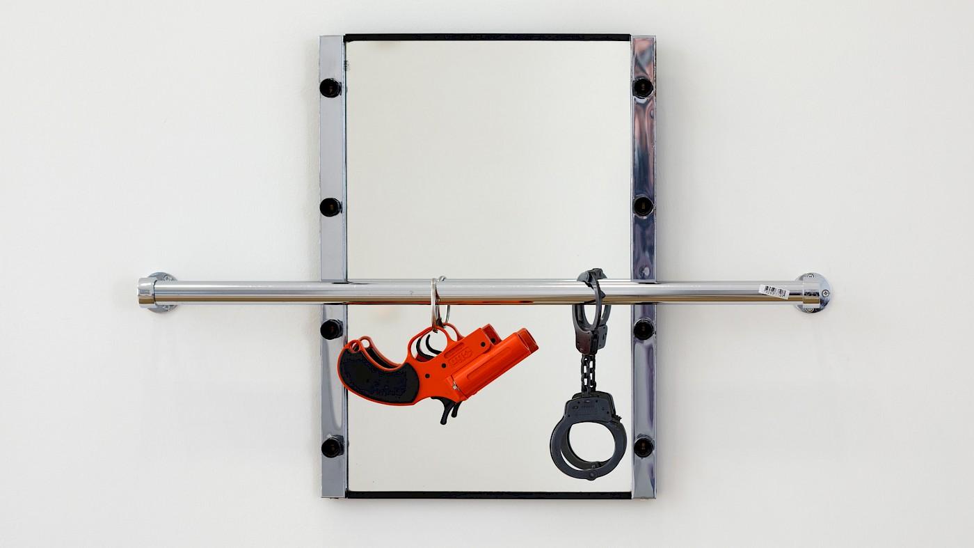 Bildbeschreibung: Ein Spiegel mit silbernem Rahmen ist an einer weißen Wand angebracht. Davor, knapp unterhalb der Mitte, befindet sich eine Metallstange, die ebenso an der Wand befestigt ist. An dieser hängen vor dem Spiegel ein kleiner orangefarbener Revolver, sowie schwarze Handschellen.  Bild: Cady Noland, The Mirror Device, 1987, Foto: Axel Schneider.