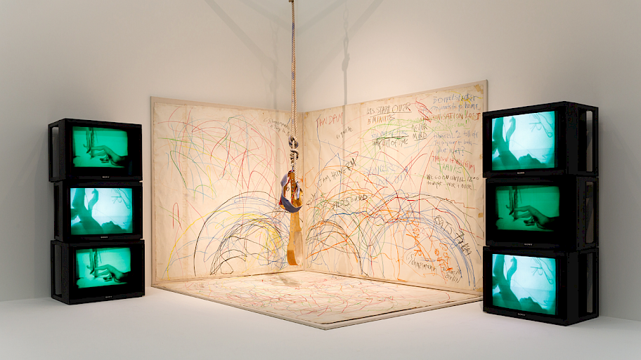 Carolee Schneemann, Up to and Including Her Limits, photo: Axel Schneider. Six black television screens, each showing a greenish image, flank three painted canvases that have been arranged to cover the corner of the room. A rope with two harnesses hangs from the ceiling.